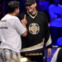 Owais Ahmed shakes talks to Phil Hellmuth after being eliminated.