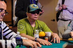 Johnny Chan Seated at a Stacked Table