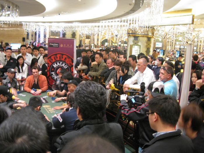 A crowd gathers around the final table of a Red Dragon main event.