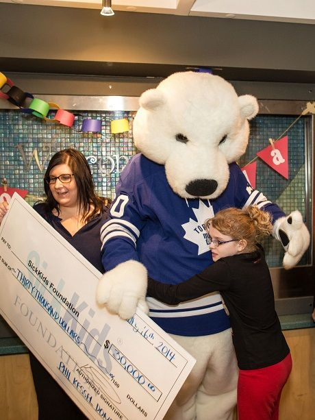 Toronto Maple Leafs' mascot Carlton the Bear presents Phil Kessel's $30,000 donation to SickKids Foundation.