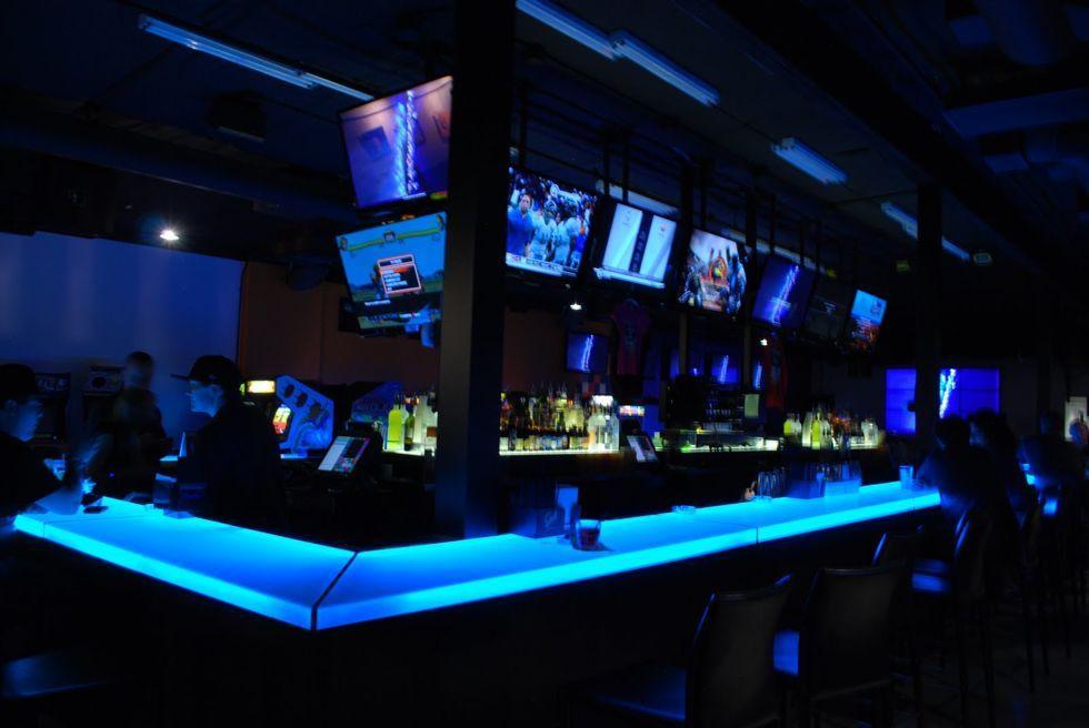 De bar met daar boven televisies waarop je moderne games kan spelen